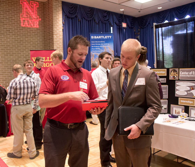 student in suit at career fair booth talking to industry representative.
